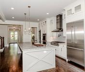 Modern Farmhouse style Kitchen open to Breakfast & Family Room in this Chamblee, GA custom home by Waterford Homes