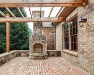 Outdoor Fireplace w/ Cedar Trellis in home built by Atlanta Home Builder Waterford Homes